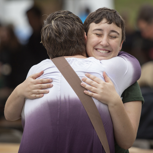 A student beams as she hugs a family  member